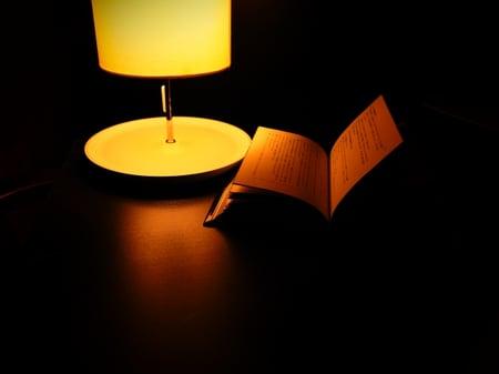 写真 暗い中、少しの明かりで読書をする様子