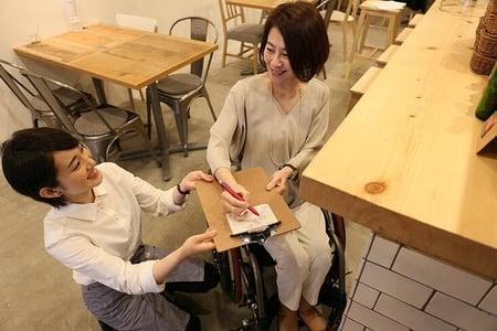 写真 店員が持ってきたクリップボードに、車椅子ユーザーが文章を書いている様子