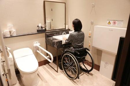 多目的トイレの手洗い場の高さが問題ないか、車椅子ユーザーが調査している写真