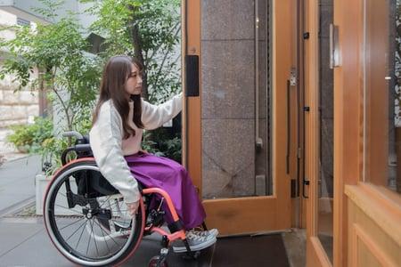 写真 車椅子ユーザーが片手でドアを開け、片手で車椅子を操作する様子