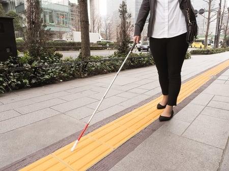 写真 白杖をもった人が誘導ブロックの上を歩く様子