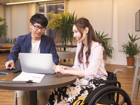 車椅子ユーザーとユーザーでない人が一緒に仕事をする様子