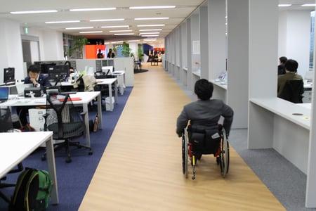 車椅子ユーザーが、オフィスの広い通路を移動する様子