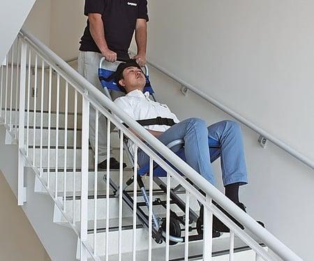 写真 非常用階段避難車に動けない人を乗せ、階段を下りている様子