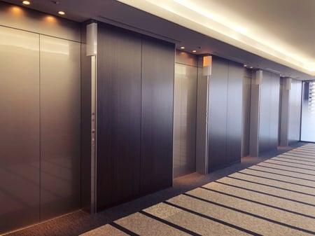 【写真】ビルのエレベーターホールに、エレベーターが4基並んでいる様子