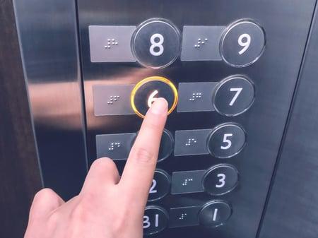 【写真】エレベーター内部の階数パネルを押している人の手
