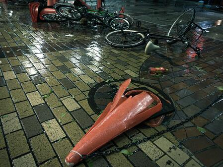 写真 台風のあと、カラーコーンや自転車が道に倒れて邪魔になっている