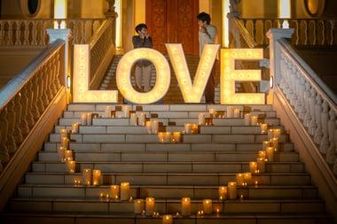 【写真】レズビアンのカップルが、LOVEと書かれたライトアップの後ろで見つめあう様子。LOVEの前には蝋燭でハートマークが作られている。