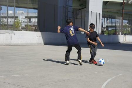 写真 小学生2人が目隠ししてボールを取り合う様子