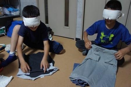 写真 アイマスクをして服を畳む小学生二人