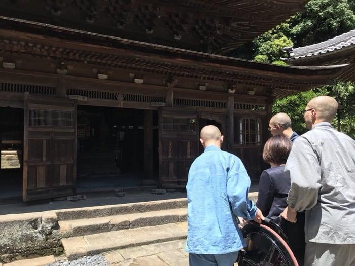 写真 階段を乗り越えるため岸田の車いすを持ち上げ和尚さんたち