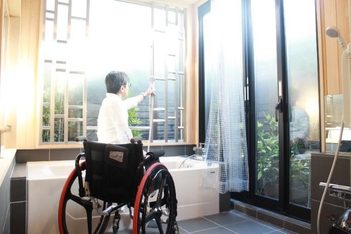 画像 車椅子ユーザーがシャワーを持つ様子