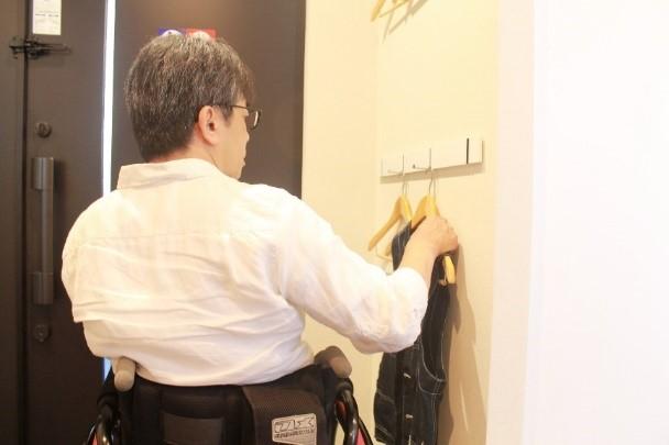 画像 車椅子ユーザーがハンガーラックを利用する様子