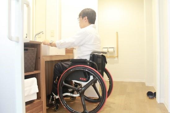 画像 車椅子ユーザーが洗面台を利用する様子