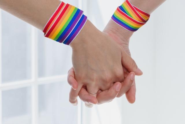 【写真】レインボーの紐を手首につけた女性二人が手をつなぐ様子